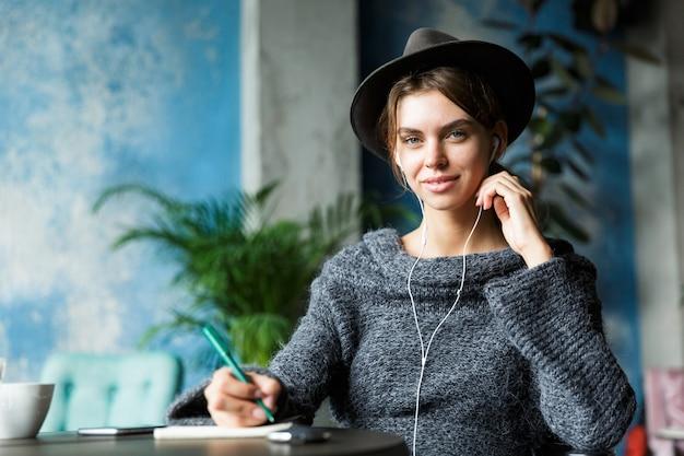 Bela jovem sorridente, vestida de suéter e chapéu, sentada na cadeira à mesa do café, ouvindo música com fones de ouvido, interior elegante, fazendo anotações