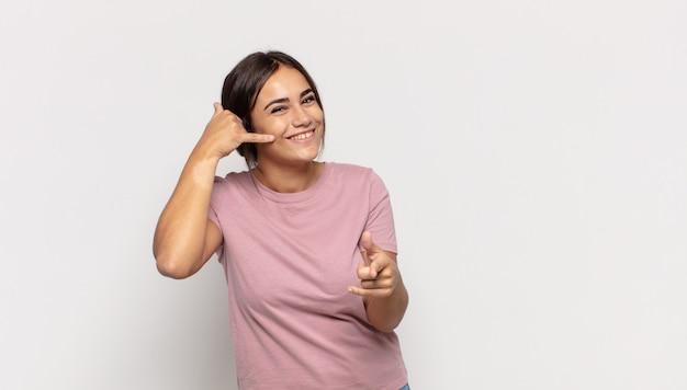 Bela jovem sorrindo alegremente e apontando para a câmera enquanto faz um gesto de