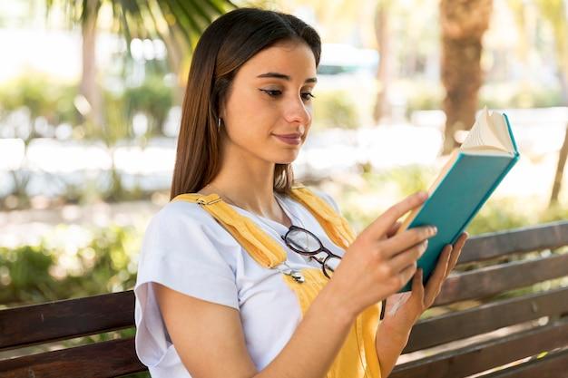 Bela jovem sorrindo e lendo o livro no parque