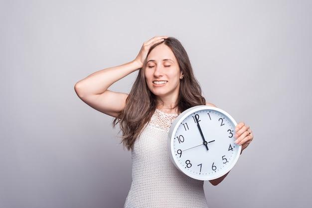 Bela jovem sorrindo e segurando um relógio branco redondo perto de uma parede cinza