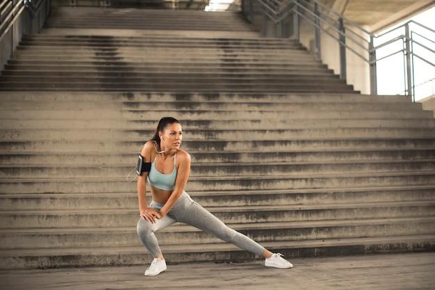 Bela jovem tendo exercício no ambiente urbano