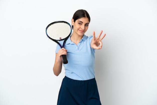 Bela jovem tenista caucasiana isolada no fundo branco feliz e contando três com os dedos