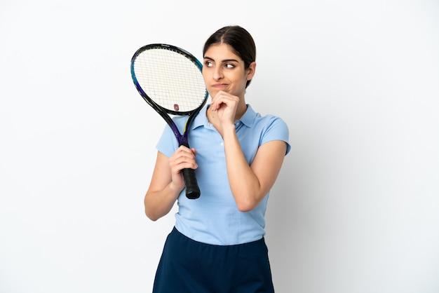 Bela jovem tenista caucasiana isolada no fundo branco, tendo dúvidas e pensando