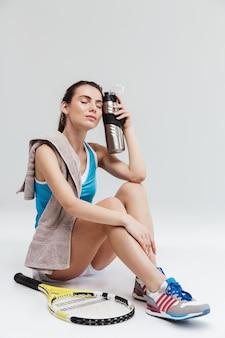 Bela jovem tenista descansando isolada sobre uma parede cinza, bebendo água
