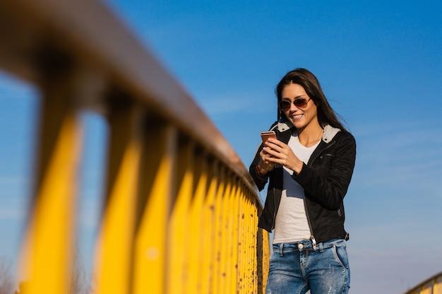 Bela jovem texting ao ar livre