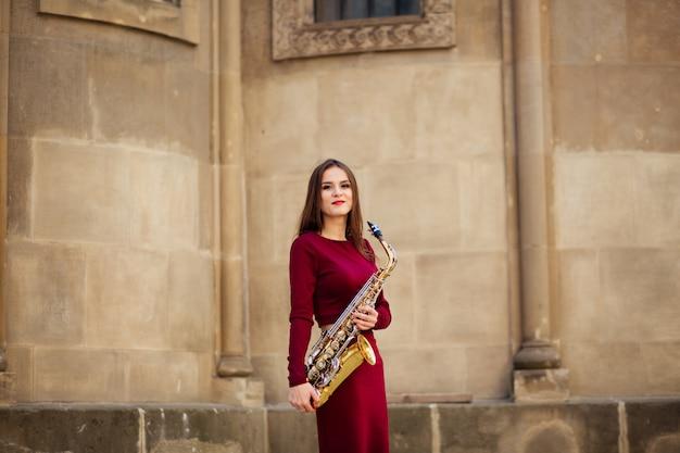 Bela jovem tocando saxofone tenor nas ruas da cidade