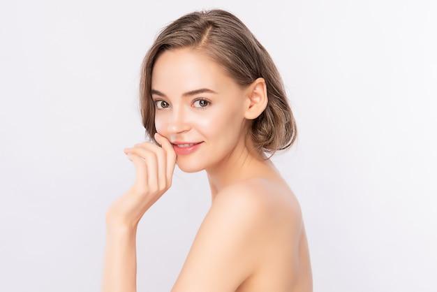 Bela jovem tocando seu rosto limpo com pele saudável fresca, isolada na parede branca, cosméticos de beleza e tratamento facial conceito