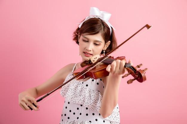 Bela jovem tocando violino sobre rosa