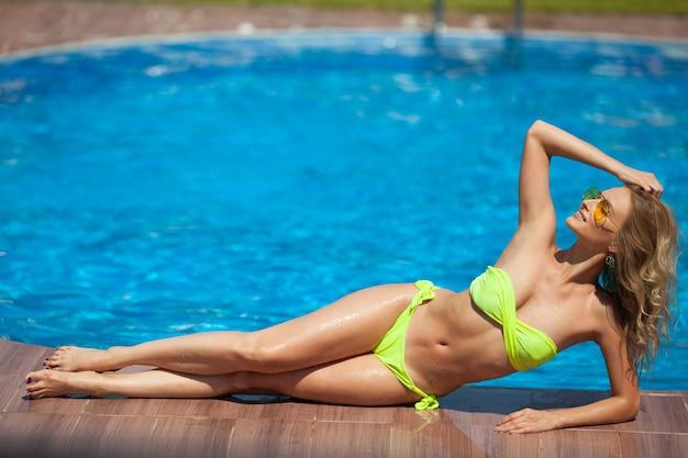 Bela jovem tomando banho de sol perto da piscina