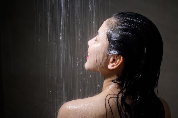 Bela jovem tomando banho em um banheiro em casa