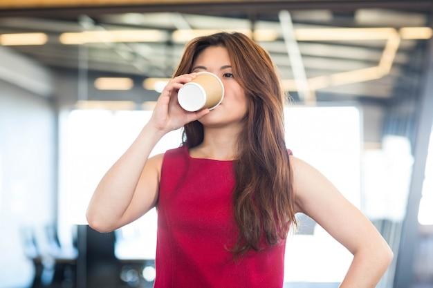 Bela jovem tomando café no escritório