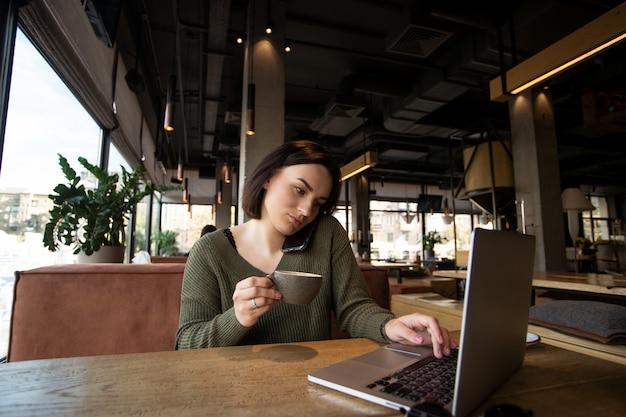 Bela jovem trabalha no laptop em um café aconchegante com grandes janelas brilhantes no fundo.