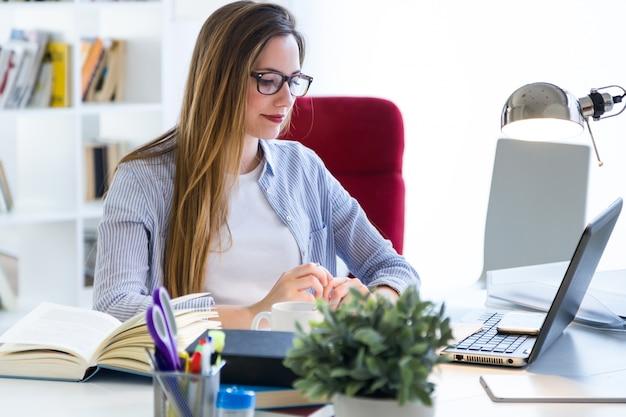 Bela jovem trabalhando com laptop em seu escritório.