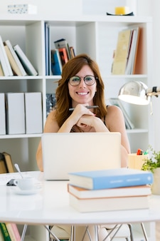 Bela jovem trabalhando com o laptop em casa.
