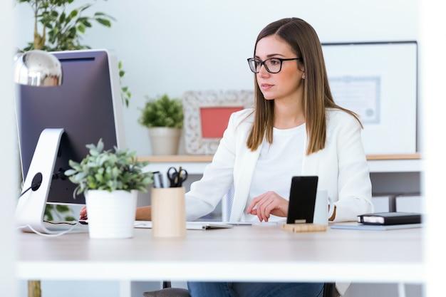 Bela jovem trabalhando com o laptop no escritório.