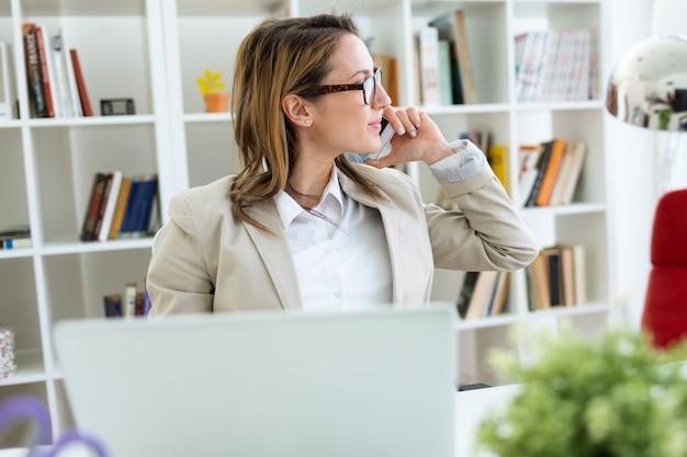 Bela jovem trabalhando com o telefone celular em seu escritório.