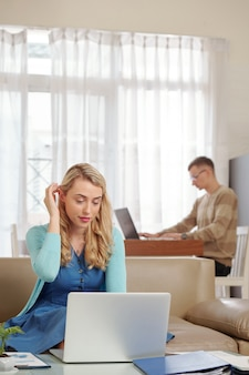 Bela jovem trabalhando com papel e documento on-line enquanto o marido programava na mesa da cozinha em segundo plano