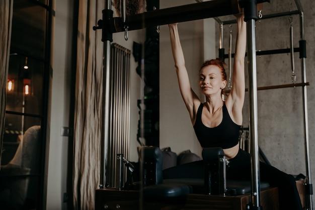 Bela jovem treinador de pilates em sportswear preto com figura atlética, fazendo exercícios de alongamento de corpo inteiro no reformador cadillac no estúdio de fitness. conceito de estilo de vida saudável e esporte dentro de casa