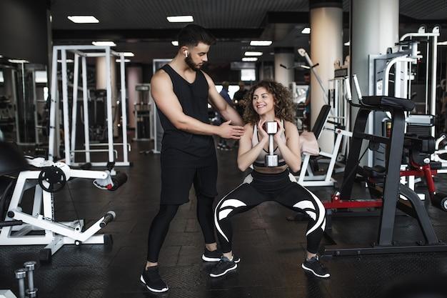 Bela jovem treinador desportivo e mulher com halteres no ginásio durante o treino