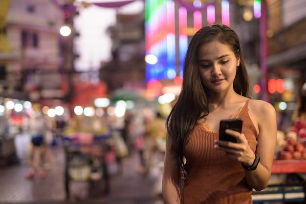 Bela jovem turista asiática usando telefone em chinatown à noite