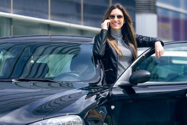 Bela jovem usando seu celular no carro.