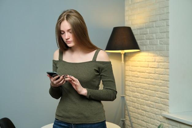Bela jovem usando smartphone para sms de texto, navegando em redes sociais