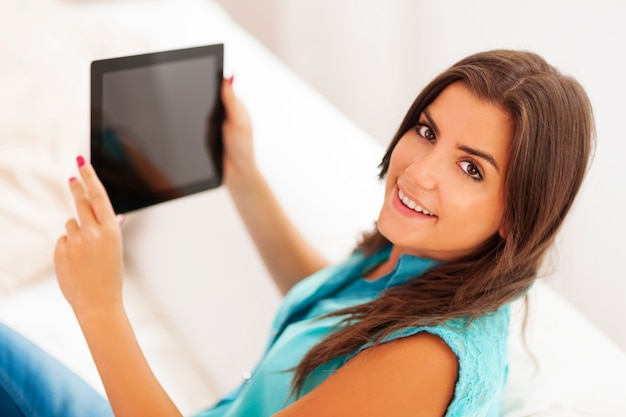 Bela jovem usando tablet digital em casa