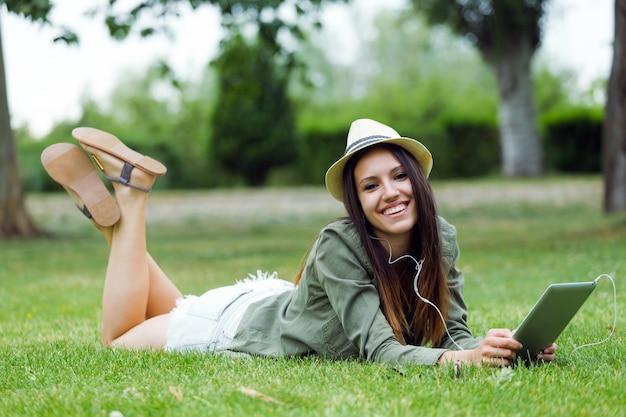 Bela jovem usando tableta digital no parque.