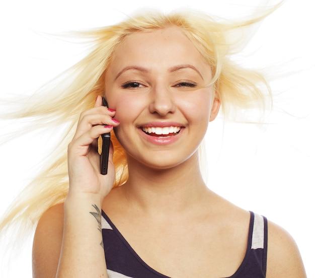 Bela jovem usando telefone celular sobre fundo branco