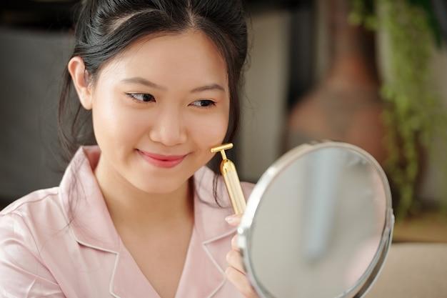 Bela jovem usando um pequeno rolo de massagem ao aplicar o soro na pele