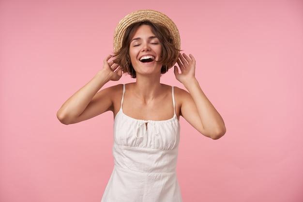 Bela jovem usando um vestido branco de verão com alças e chapéu de boater, mantendo os olhos fechados enquanto posa