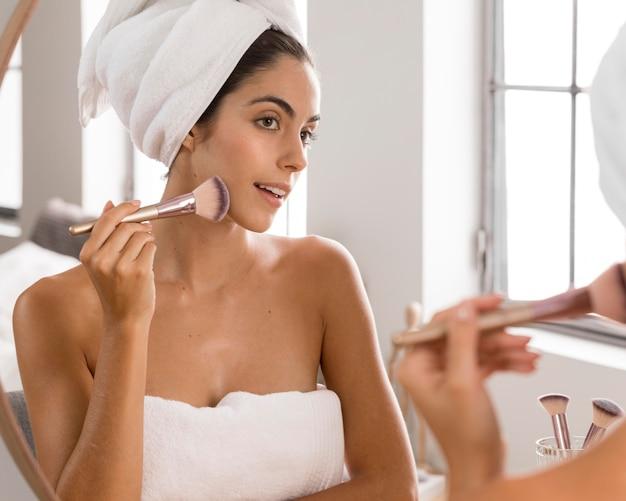 Bela jovem usando uma vista frontal de um pincel de maquiagem
