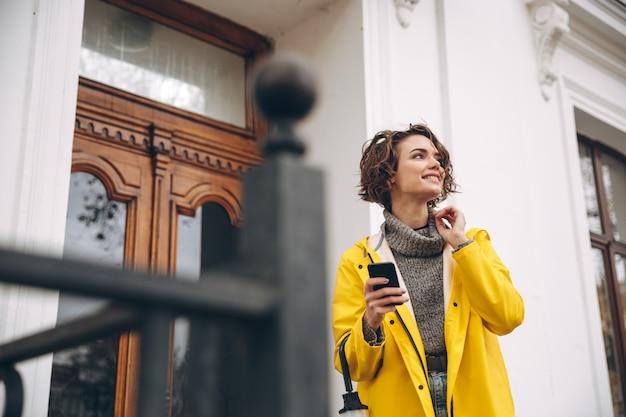 Bela jovem vestida de capa de chuva conversando