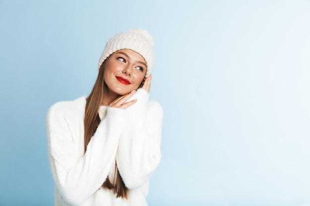 Bela jovem vestindo blusa e chapéu, olhando para longe