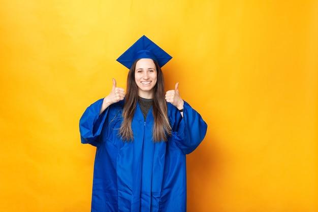 Bela jovem vestindo roupas de formatura azuis aparecendo os polegares.