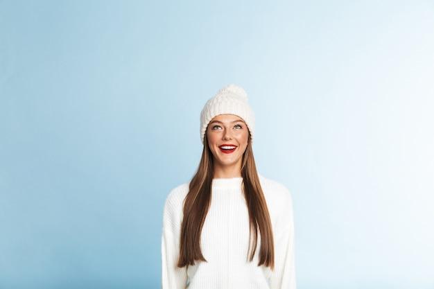 Bela jovem vestindo suéter e chapéu, olhando para cima