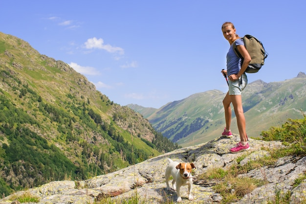 Bela jovem viajando com mochila na montanha