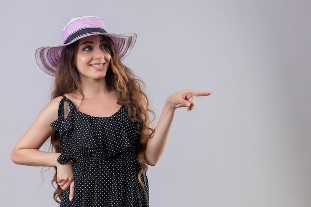 Bela jovem viajante com chapéu de verão apontando para alguém sorrindo em pé sobre um fundo branco