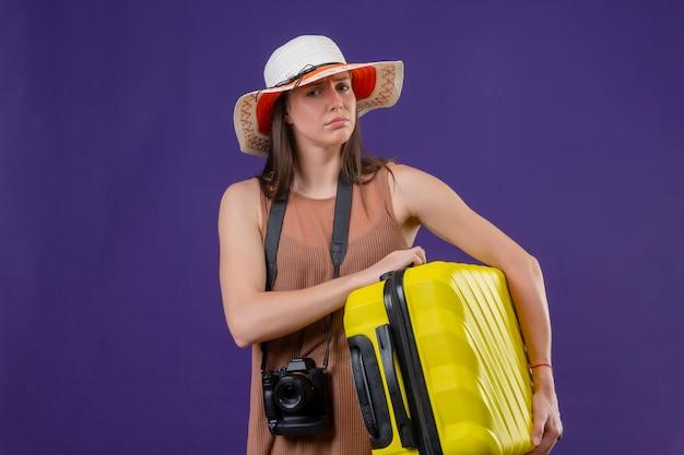 Bela jovem viajante com chapéu de verão com mala amarela e câmera parecendo confusa, sem resposta em pé sobre um fundo roxo