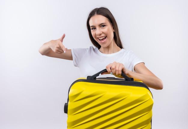 Bela jovem viajante segurando uma mala e sorrindo alegremente mostrando os polegares para cima