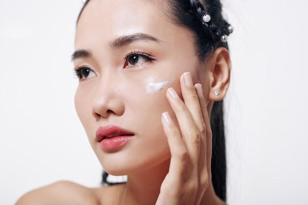 Bela jovem vietnamita aplicando creme hidratante e rejuvenescedor no rosto