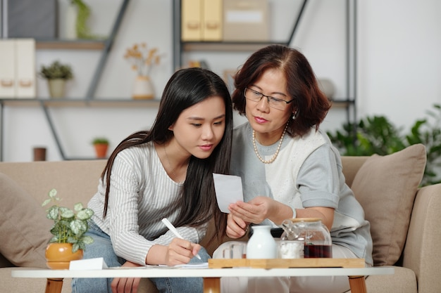 Bela jovem vietnamita checando contas e ajudando a mãe com a contabilidade doméstica