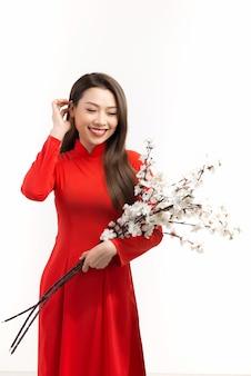 Bela jovem vietnamita segurando galhos de pêssego em flor