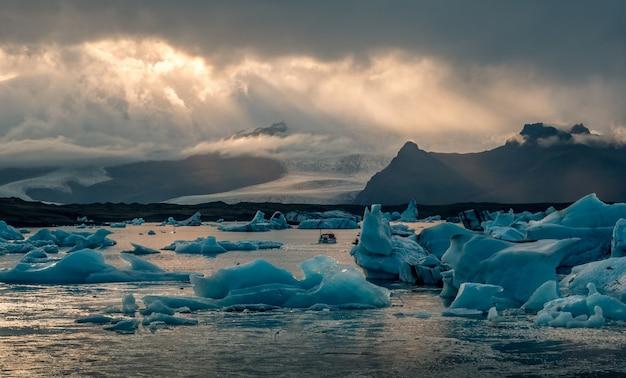 Bela lagoa da geleira jokulsarlon na islândia, com raios de sol em um céu escuro e nublado
