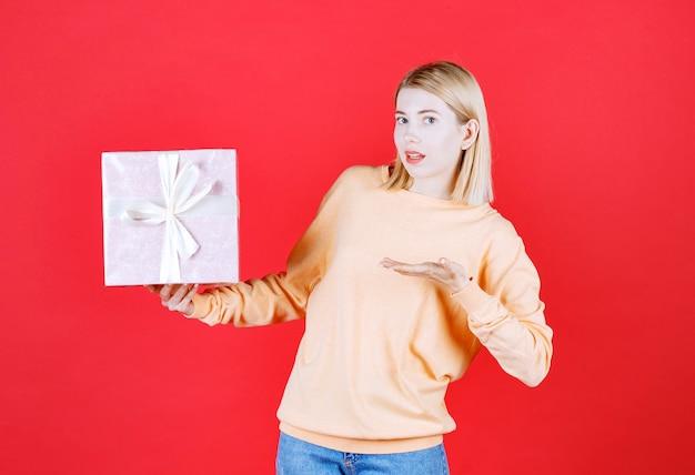 Bela loira apontando para a caixa de presente que está segurando acima da mão em frente à parede vermelha