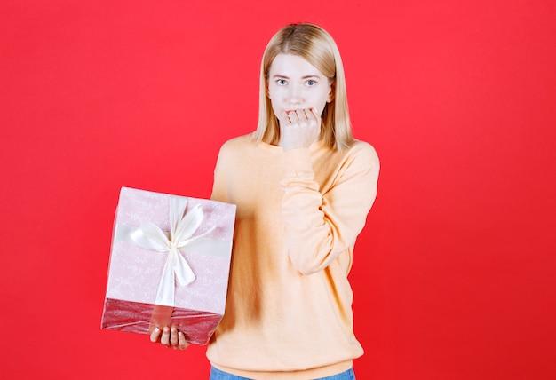 Bela loira colocando a mão perto da boca enquanto segura a caixa de presente na frente da parede vermelha