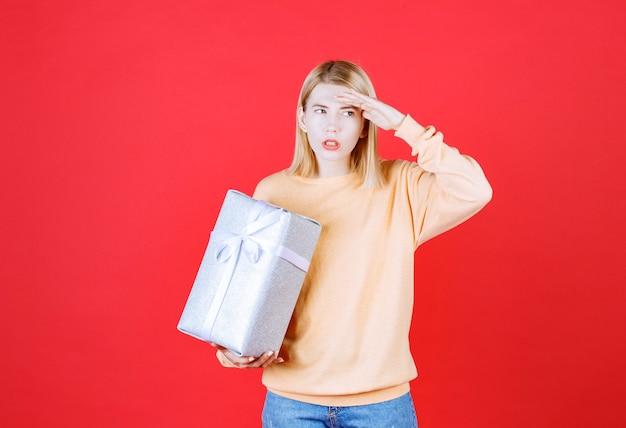 Bela loira colocando a mão perto da testa enquanto segura a caixa de presente