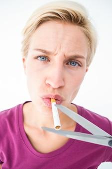 Bela loira cortando um cigarro