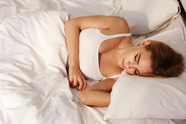 Bela loira duvida, deitada na cama branca