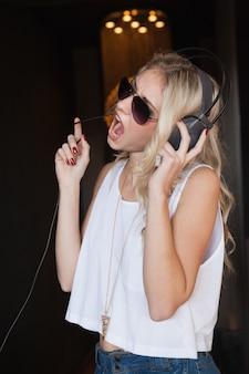 Bela loira em óculos de sol ouvindo musica e cantando
